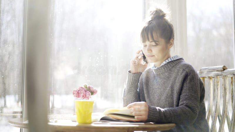 Una muchacha morena linda seria joven está teniendo una llamada en el café foto de archivo