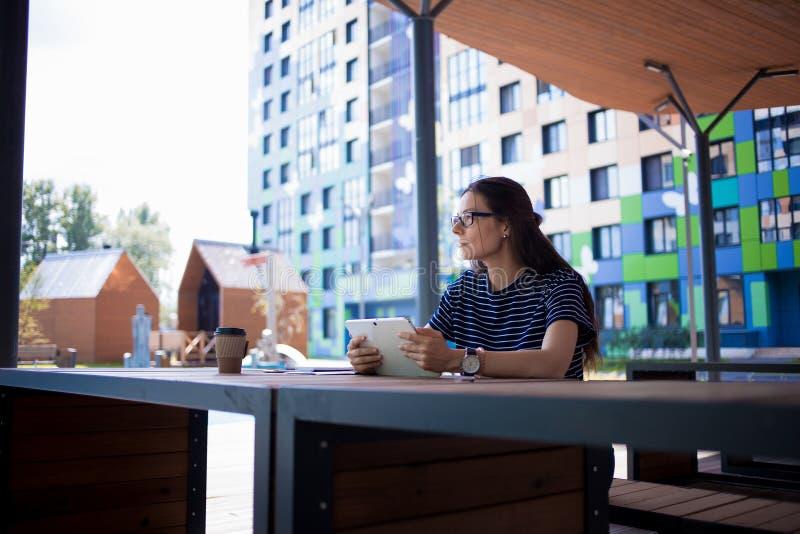 Una muchacha morena seria, freelancer, con el reloj grande, trabaja en una tabla de madera en la tableta, con los artilugios y lo imágenes de archivo libres de regalías