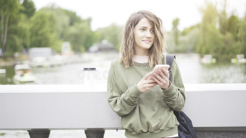Una muchacha morena sonriente está escuchando una música al aire libre que bebe una taza de café foto de archivo libre de regalías