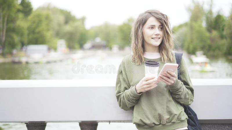 Una muchacha morena sonriente está escuchando una música al aire libre que bebe una taza de café fotografía de archivo