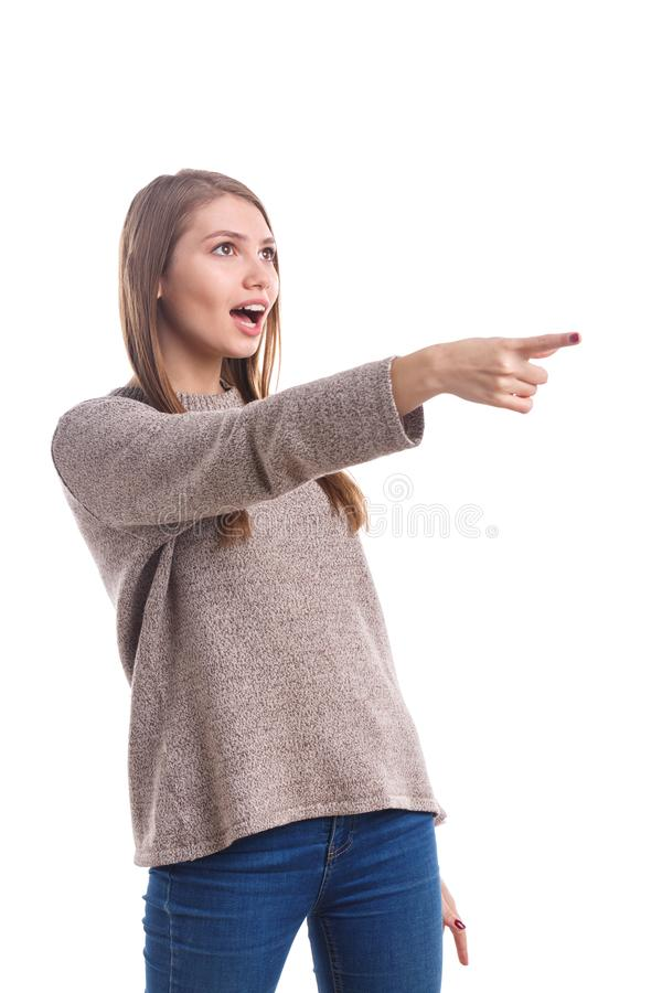 Una muchacha muestra una emoción de la sorpresa, señalando con el dedo índice delante de ella Aislado en el fondo blanco foto de archivo