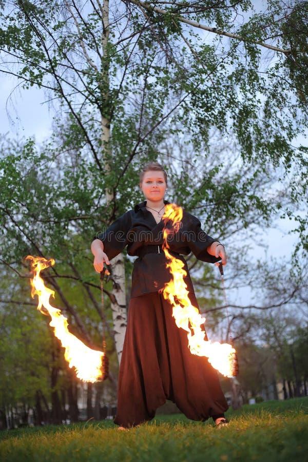 Una muchacha muestra una demostración del fuego en la naturaleza fotografía de archivo