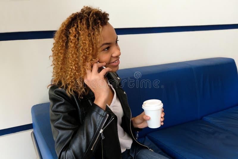 Una muchacha negra hermosa en una blusa blanca y una chaqueta de cuero con un vidrio de café que se sienta en un sofá azul, habla foto de archivo