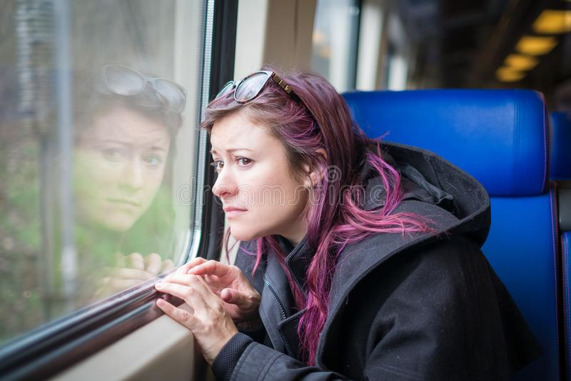 Una muchacha nerviosa joven en un tren foto de archivo