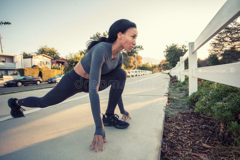 Una muchacha oscura deportiva de la piel que estira en la trayectoria de la bici en la ciudad fotos de archivo