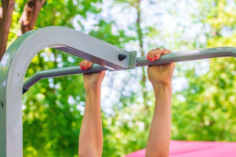 Una muchacha pasa los estándares para levantar en una barra horizontal en el día soleado del parque imagen de archivo libre de regalías