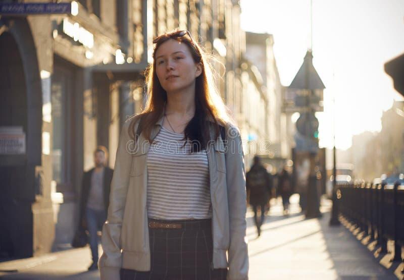 Una muchacha pelirroja camina a lo largo de la calle iluminada por el sol foto de archivo libre de regalías