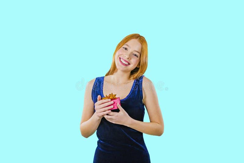 Una muchacha pelirroja hermosa en un vestido azul de igualación del terciopelo está sosteniendo una pequeña caja con un regalo qu foto de archivo libre de regalías
