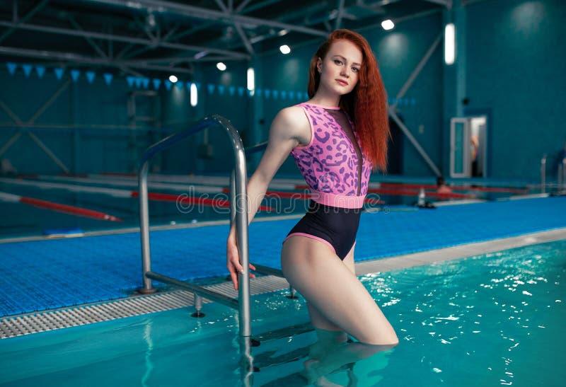 Una muchacha pelirroja hermosa se coloca en los pasos de la escalera de la piscina Contratan a una mujer a una forma de vida sana fotografía de archivo