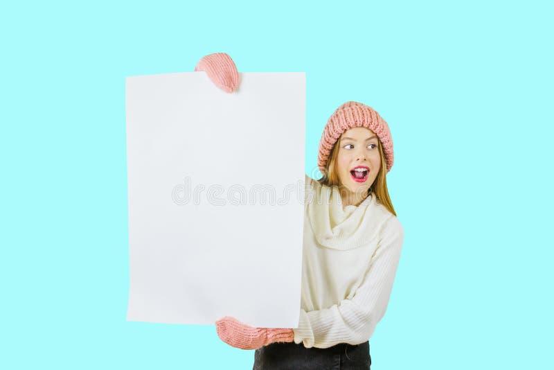 Una muchacha pelirroja joven en un sombrero rosado hecho punto y manoplas sostiene un cartel blanco grande con ambas manos y mira foto de archivo