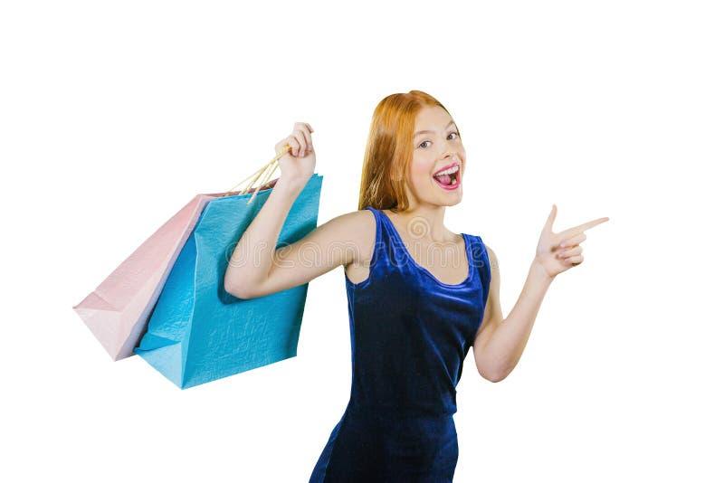 Una muchacha pelirroja joven hermosa en un vestido lleva a cabo tres paquetes, aumentando su mano con los paquetes, y con ella imagen de archivo libre de regalías