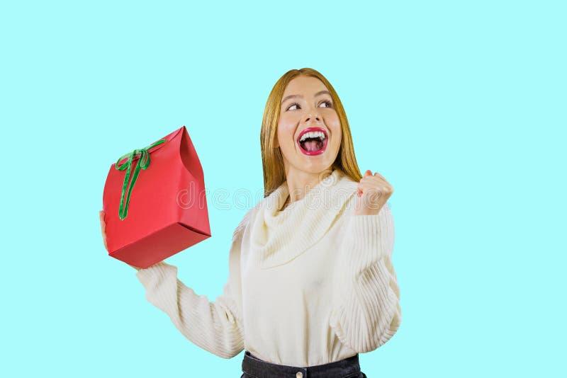 Una muchacha pelirroja linda hermosa que sostiene el bolso del regalo con una mano que sostiene una caja roja con una cinta verde fotografía de archivo libre de regalías