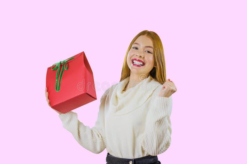 Una muchacha pelirroja linda hermosa que sostiene el bolso del regalo con una mano en una caja roja con un aumento verde de la ci imagenes de archivo