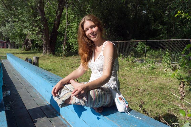 Una muchacha pelirroja se sienta a piernas cruzadas en un banco azul de madera viejo contra un fondo de árboles foto de archivo libre de regalías