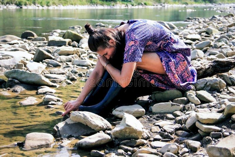 Una muchacha pensativa se sienta en el banco de un río y de los juegos de la montaña con agua fotos de archivo