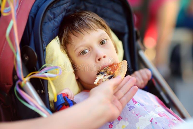 Una muchacha poco discapacitada de la pizza de alimentación de la madre en una silla de ruedas Parálisis cerebral del niño inclus foto de archivo