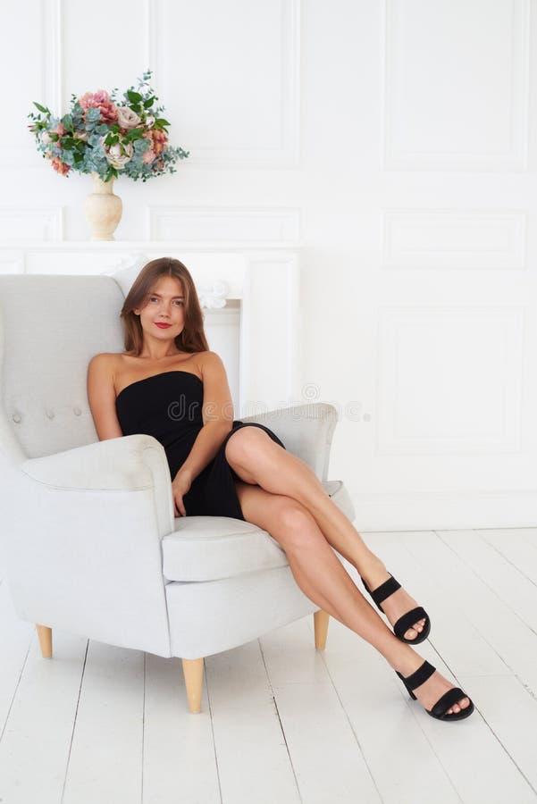 Una muchacha preciosa en negro se está sentando en una butaca blanca acogedora foto de archivo