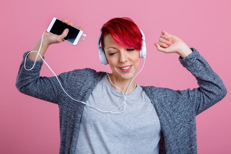 Una muchacha que escucha la música en los auriculares con el teléfono y que baila con sus manos para arriba En un fondo rosado fotografía de archivo