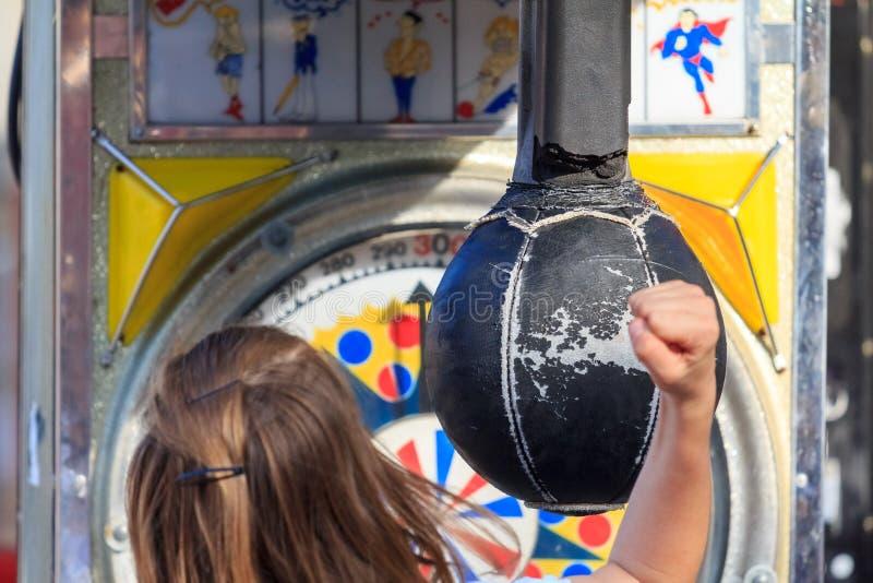 Una muchacha que golpea un bolso de sacador del parque de atracciones fotografía de archivo
