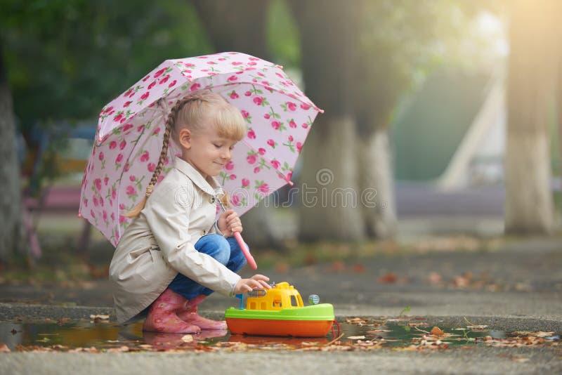 Una muchacha que juega en el charco con el barco después de lluvia imagen de archivo