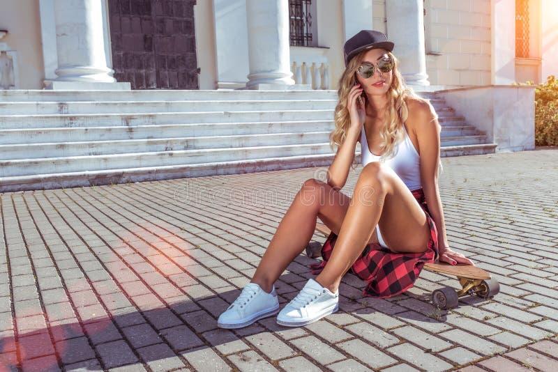 Una muchacha que la gorra de béisbol hace la llamada telefónica, monopatín del verano se sienta en ciudad, uso en línea de Intern imágenes de archivo libres de regalías
