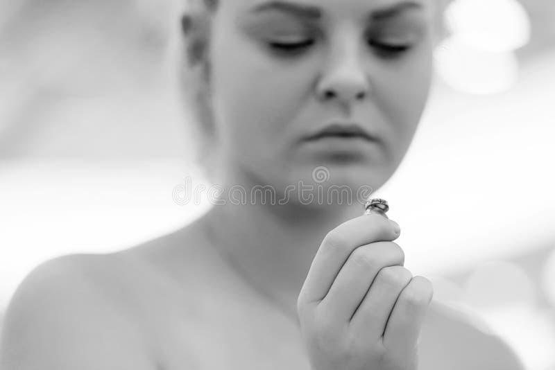 Una muchacha que lleva a cabo un anillo de bodas dudoso fotografía de archivo libre de regalías