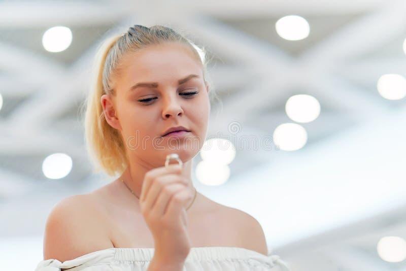 Una muchacha que lleva a cabo un anillo de bodas dudoso imagen de archivo