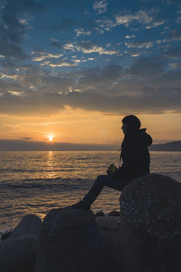 Una muchacha que mira una salida del sol sobre el mar en Varna imagen de archivo libre de regalías