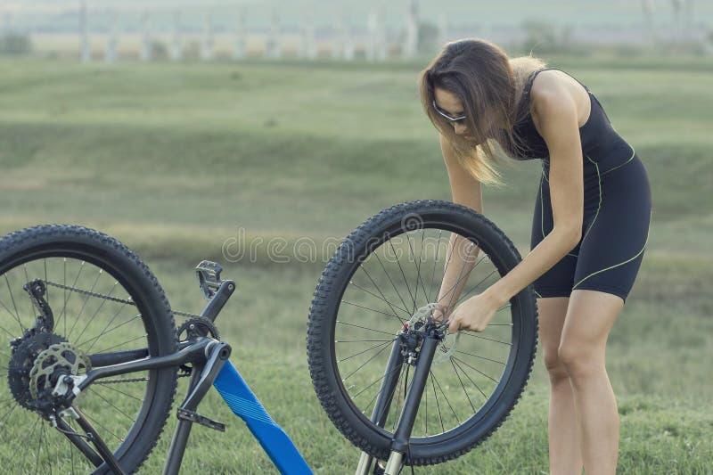 Una muchacha que monta una bici de montaña en una carretera de asfalto, retrato hermoso de un ciclista foto de archivo