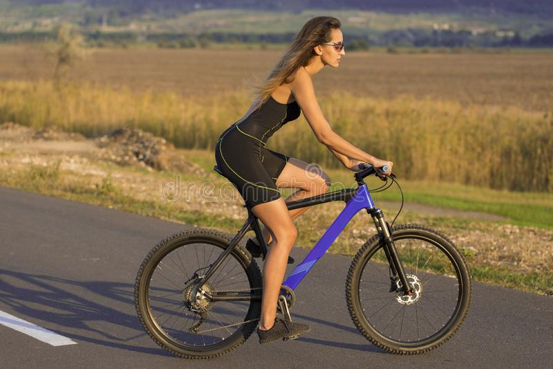 Una muchacha que monta una bici de montaña en una carretera de asfalto, retrato hermoso de un ciclista foto de archivo libre de regalías