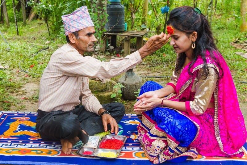 Una muchacha que recibe Tika y bendiciones de su padre en Dashain F foto de archivo libre de regalías
