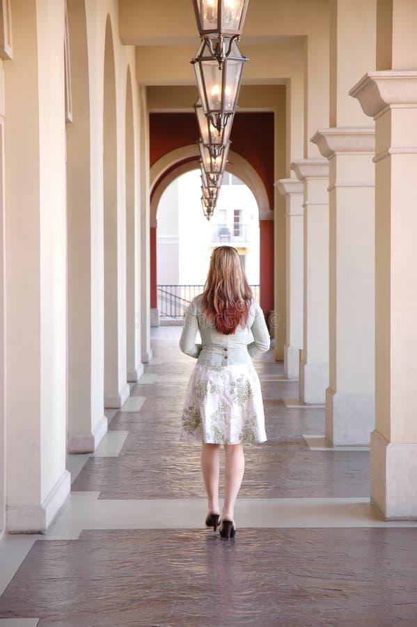 Una muchacha que recorre en un vestíbulo fotos de archivo