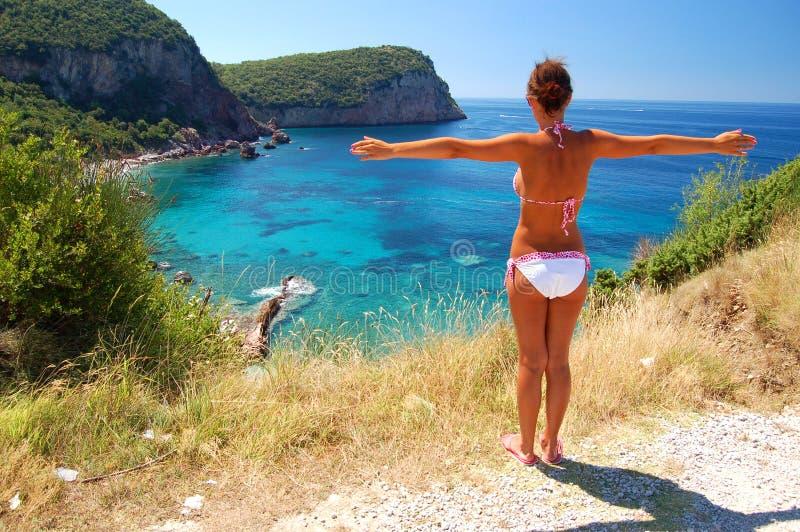 Una muchacha que se coloca sobre la playa rocosa imagen de archivo libre de regalías