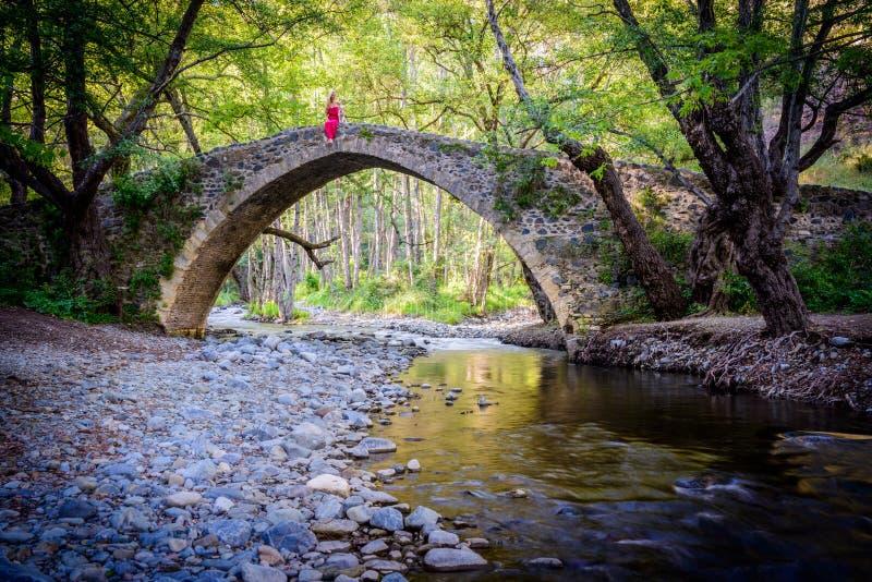 Una muchacha que se sienta en el puente de los kelefos, Chipre, 2 fotografía de archivo