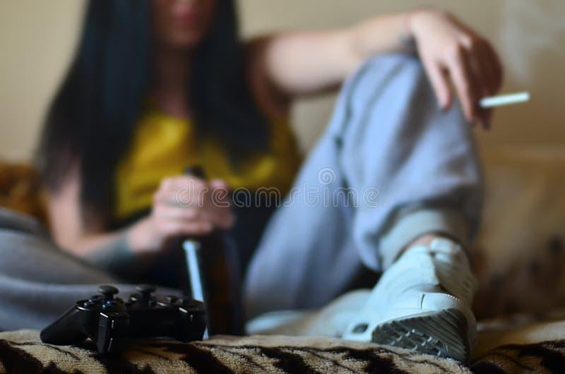 Una muchacha que se sienta en el sofá, fumando un cigarrillo, cerveza de consumición fotos de archivo libres de regalías