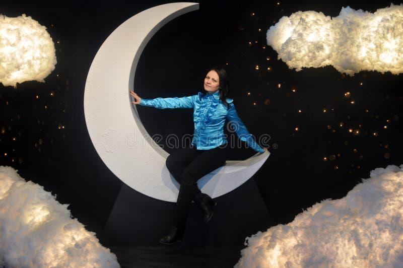 Una muchacha que se sienta en la luna y las nubes fotos de archivo