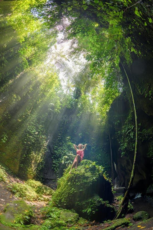 Una muchacha que se sienta en una roca en la cascada de Tukad Cepung en Bali 2 fotografía de archivo