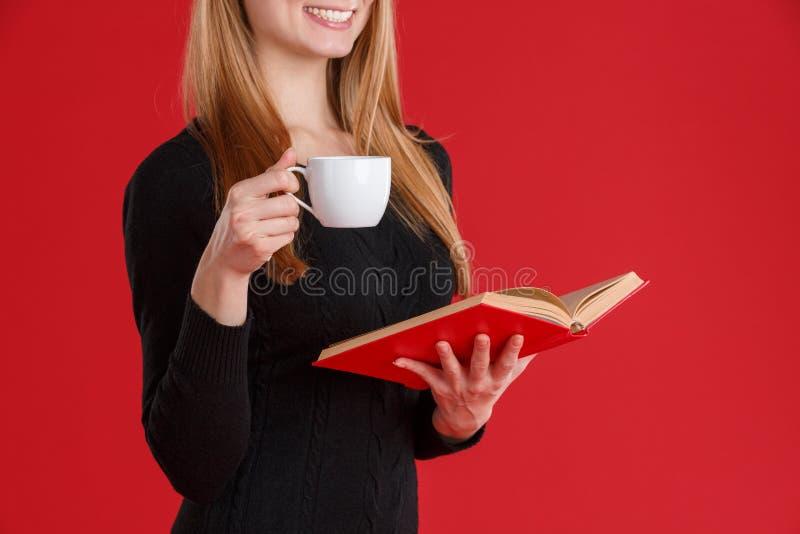 Una muchacha que sostiene en una mano un libro abierto y una taza con una bebida y una sonrisa Fondo rojo Primer imagenes de archivo