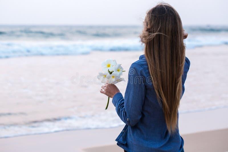 Una muchacha que sostiene una flor fotos de archivo