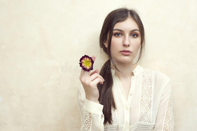 Una muchacha que sostiene la flor del primerose que finge fumar imagen de archivo