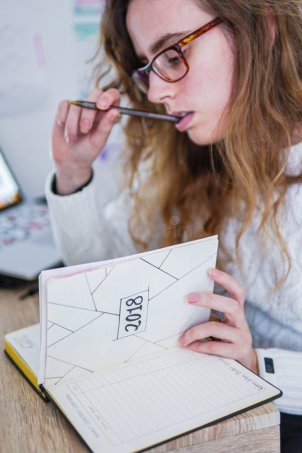 Una muchacha que trabaja en su escritorio imagenes de archivo