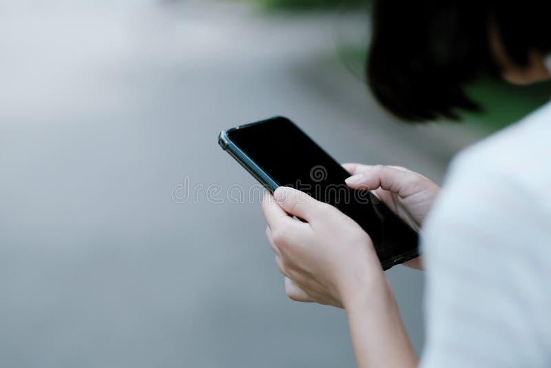 Una muchacha que usa el smartphone negro para las compras en línea foto de archivo