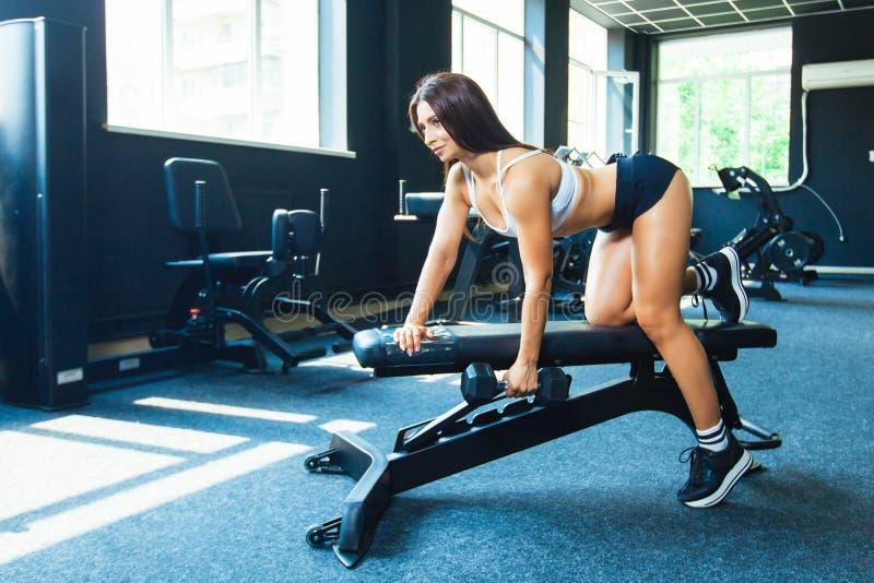 Una muchacha realiza una pesa de gimnasia con una mano en la cuesta usando un banco ejercicio en los músculos traseros más amplio imagenes de archivo