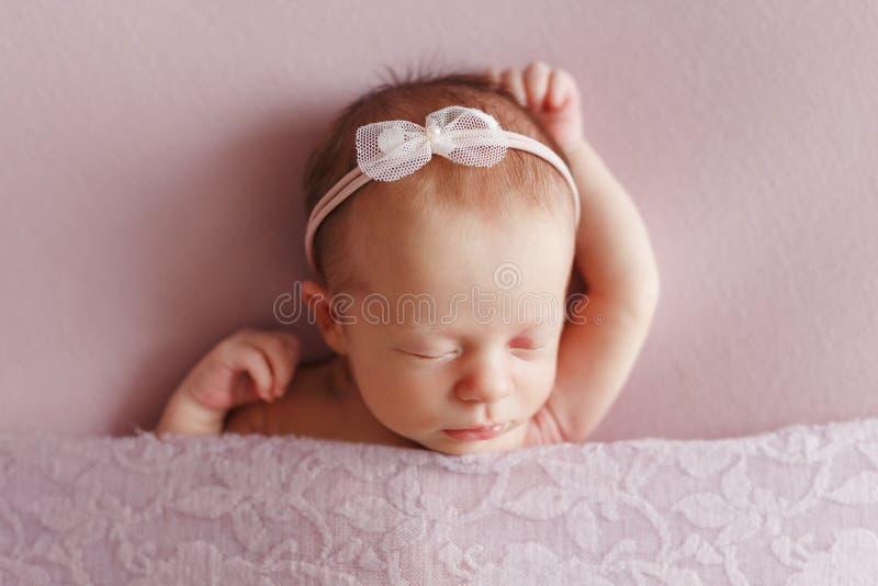 Una muchacha recién nacida linda con un arco en su cabeza dormida en una parte posterior del rosa imagen de archivo