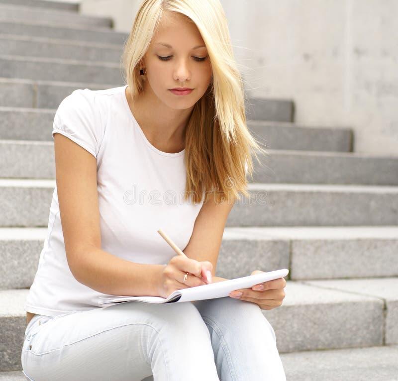 Una muchacha rubia atractiva está escribiendo una nota imagenes de archivo