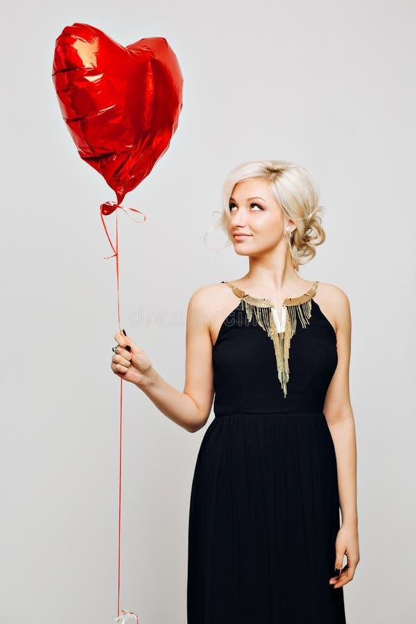 Una muchacha rubia atractiva joven hermosa con el pelo rubio rizado en un vestido negro elegante largo con joyería dorada es imagen de archivo libre de regalías