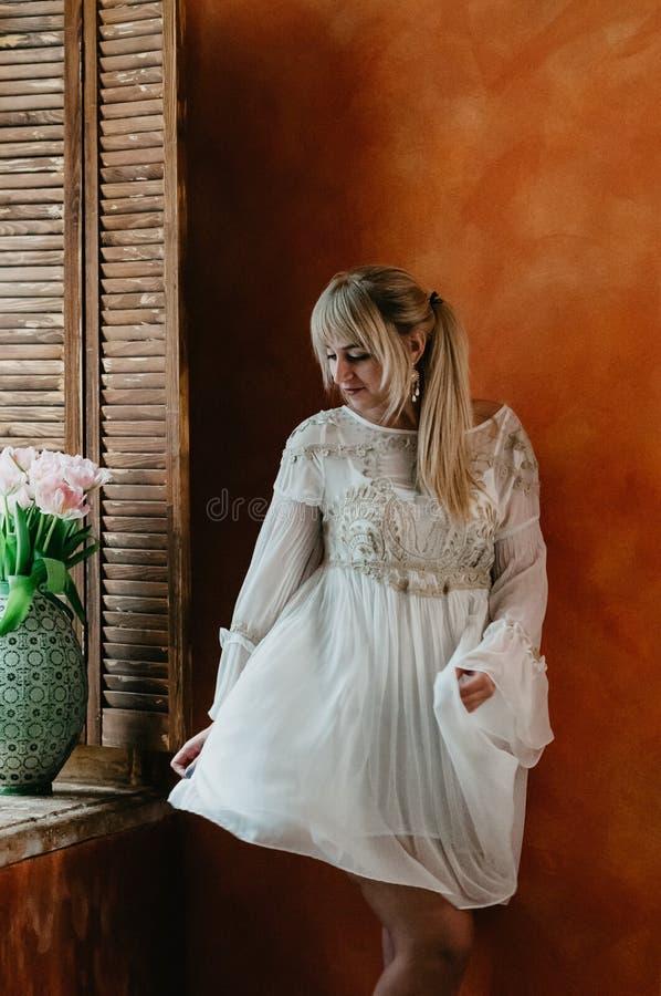 Una muchacha rubia en el baile blanco por la ventana, flores del vestido fotos de archivo libres de regalías