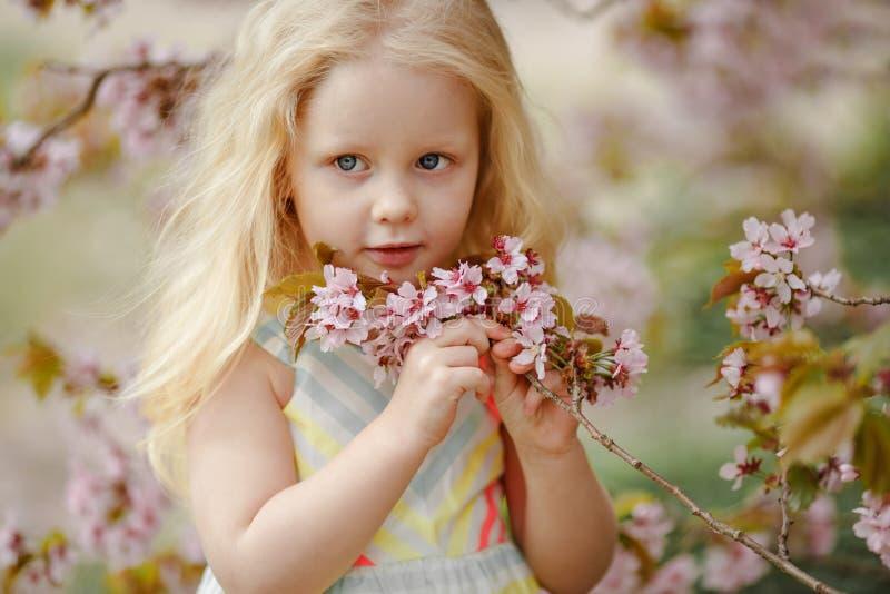 Una muchacha rubia encantadora linda con el pelo enorme que sonríe en un sak rosado fotografía de archivo