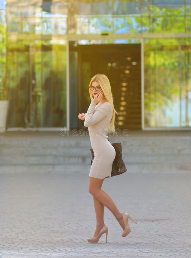 Una muchacha rubia hermosa en un vestido y vidrios está caminando abajo de la calle y está hablando en el teléfono cerca del cent foto de archivo