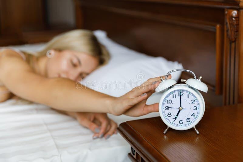Una muchacha rubia hermosa joven despierta por la mañana, y despierta su despertador La muchacha despierta por la ma?ana A fotos de archivo libres de regalías